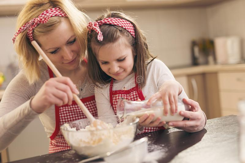 Mother and daughter kneading a pizza dough royalty free stock photos