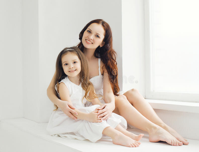 Beautiful mother and daughter at home in white room stock photo