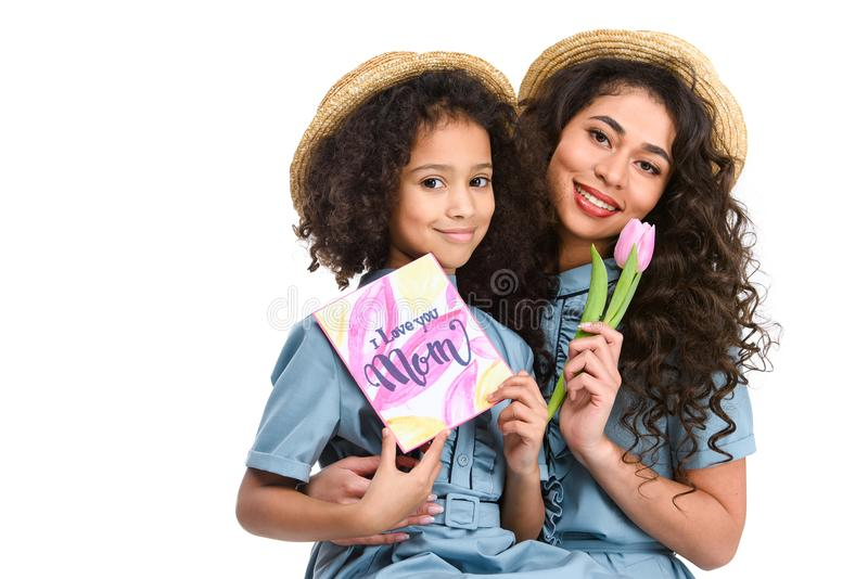 Beautiful mother and daughter with mothers day greeting card and flower. Isolated on white royalty free stock images