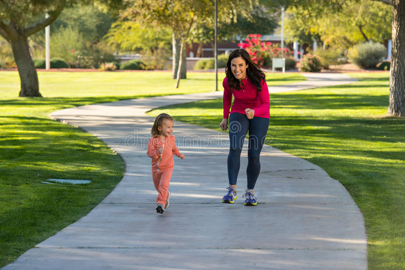 Beautiful mother and daughter running in the neighborhood stock photos