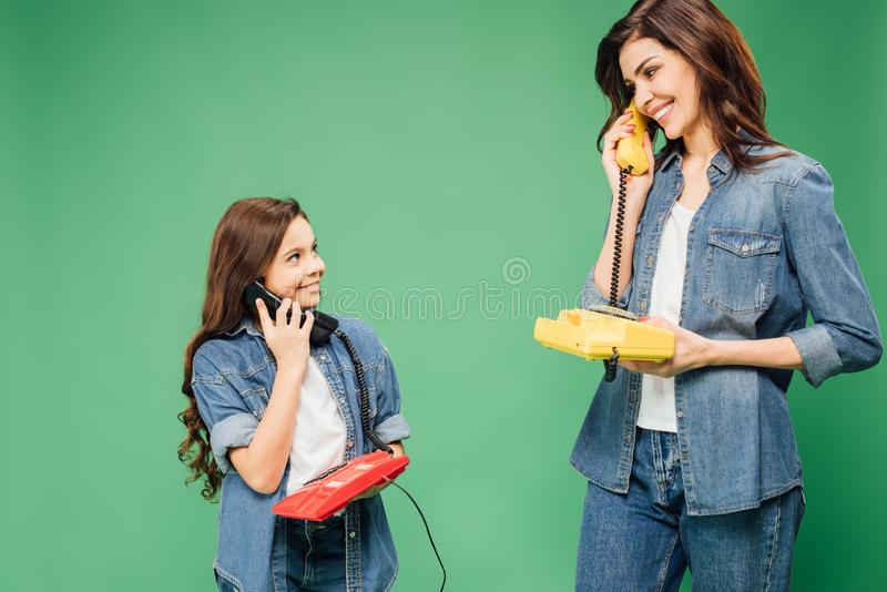 Beautiful mother and daughter talking on vintage telephones isolated. On green stock photos