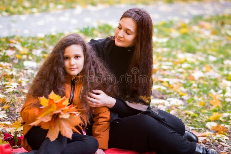 Beautiful mother and daughter teenager on a walk in the fall. A child in orange jacket, a woman in black clothes. They are sitting stock photo