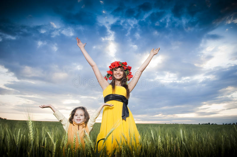 Beautiful mother and daughter in the wheat field royalty free stock photo