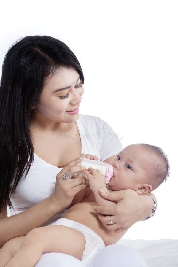 Beautiful mother feeding her baby on studio stock photography
