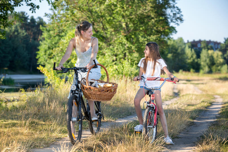 Beautiful mother going to picnic with daughter on bicycles stock photo