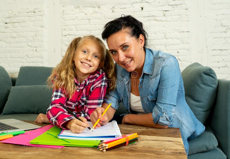 Beautiful mother helping her young blonde cute sweet girl to do homework at home in homework parenting and education concept stock image