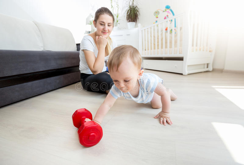 Beautiful mother with her baby boy exercising with dumbbells on. Young beautiful mother with her baby boy exercising with dumbbells on floor at living room royalty free stock photo