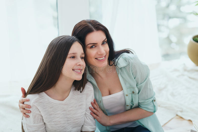 Beautiful mother and her cute daughter smiling and posing at home. Beautiful mother and her pretty daughter teenager smiling and posing at home stock photo