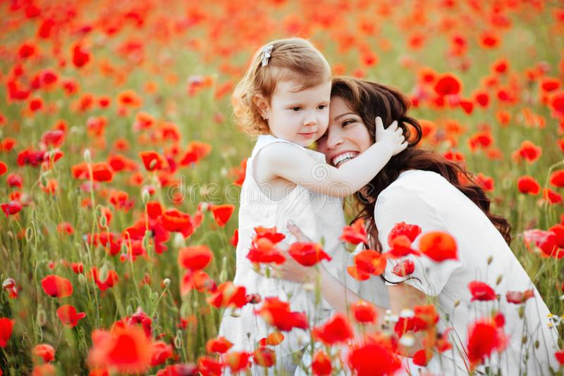 Mother and daughter playing in flower field stock images