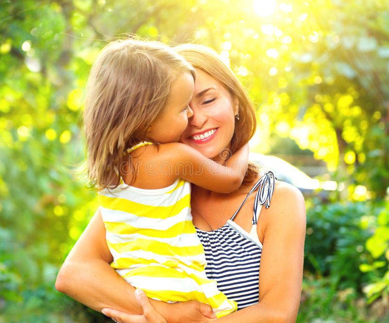 Beautiful mother and her little daughter. Playing in summer park together stock image