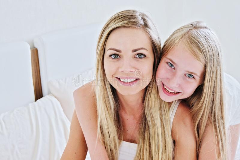 Beautiful mother and her pretty daughter teenager smiling at home. Beautiful mother and her pretty daughter teenager smiling and posing at home stock images