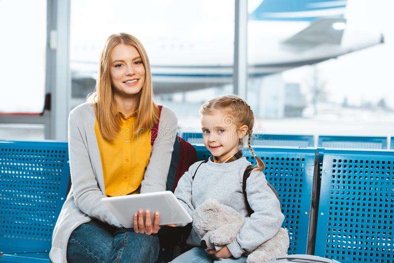 Beautiful mother holding digital tablet and sitting in airport stock images