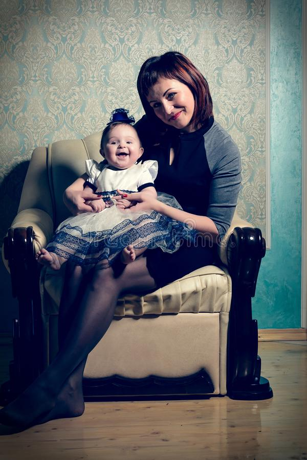A beautiful mother holds up a small child in her dress and hat royalty free stock images