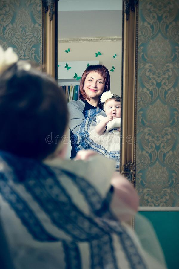 A beautiful mother holds up a small child in her dress and hat stock photography