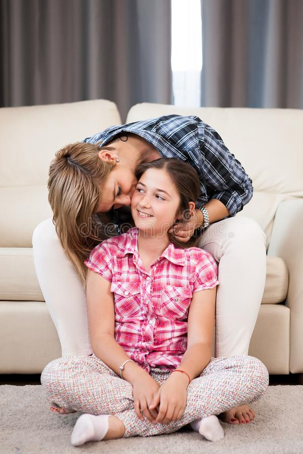 Beautiful mother kisses her daughter forehead. While she is sitting on the couch and the child is sitting on the floor in the living room royalty free stock photos