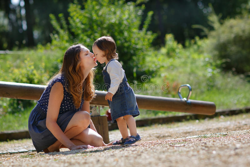 Beautiful mother and little daughter on playground royalty free stock image