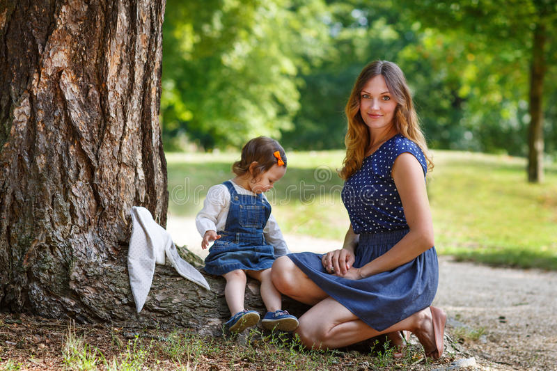 Beautiful mother and little daughter walking in summer park stock photo