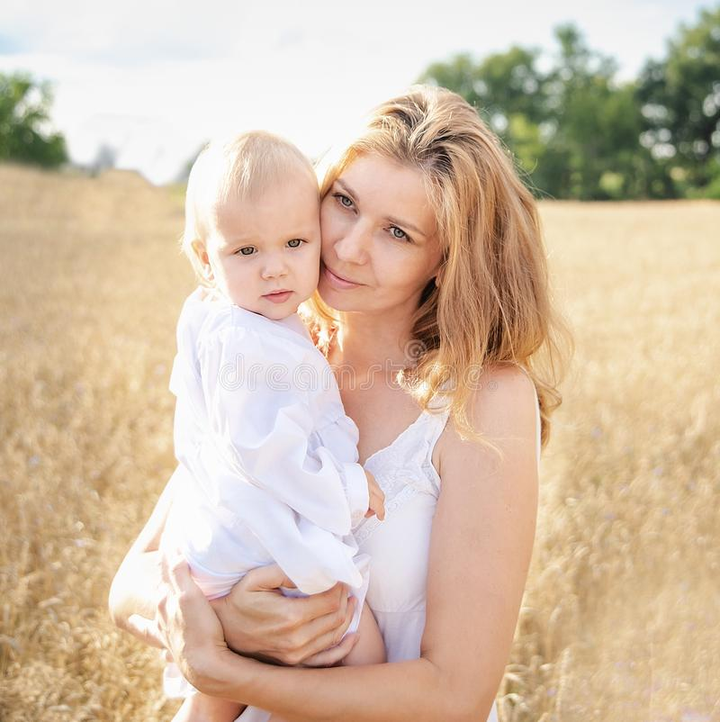Beautiful elegant mother and little daughter wheat field, family royalty free stock photography