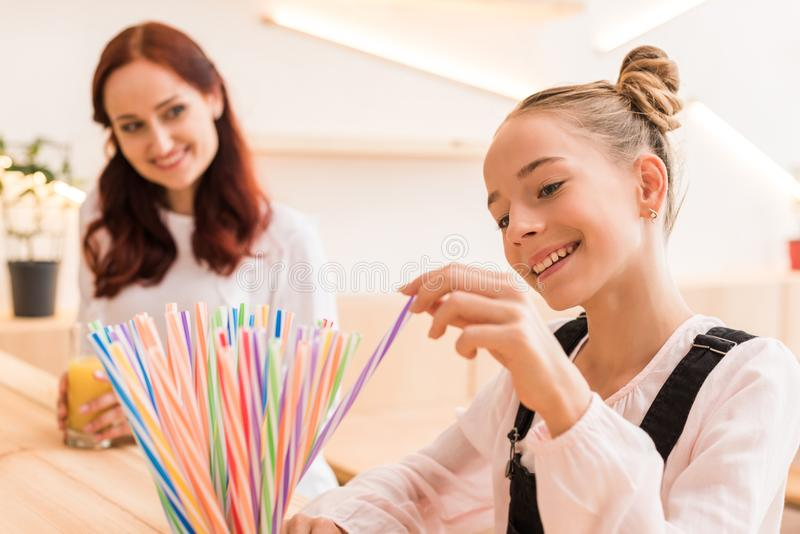 Teen girl choosing straw in cafe stock photography
