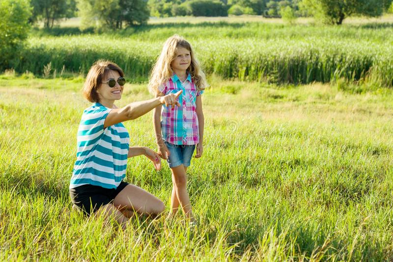 . Beautiful mother outdoors with happy daughter child. A woman shows a little girl a finger in the distance. Loving family royalty free stock photo