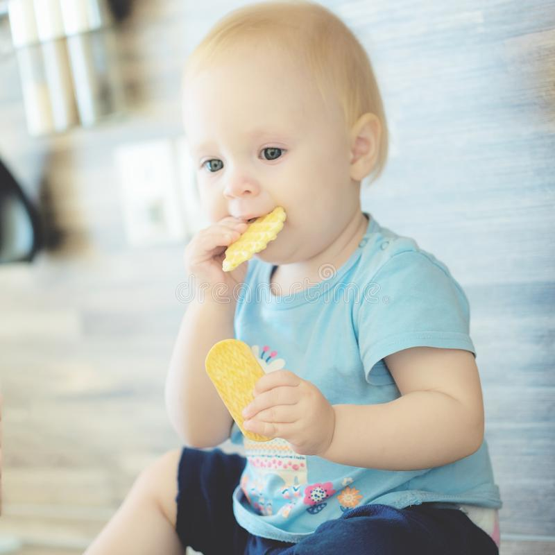 Beautiful mother playing with her beautiful child , the child eats the cookie and laughs royalty free stock photo