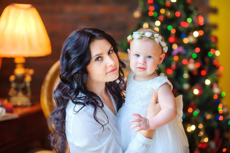 Beautiful mother playing with her little daughter sitting near the festive Christmas tree stock photo