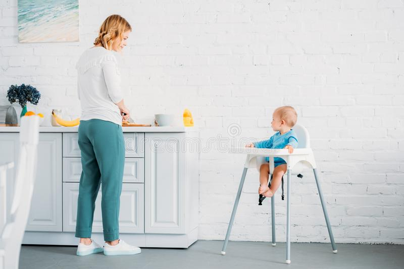 Beautiful mother preparing dinner for her little child. While he sitting in feeding chair at kitchen royalty free stock image