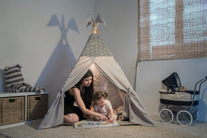 Beautiful mother reading to daughter in a teepee. In the playroom when the light bulb in the evening on the floor. concept listal, people and care royalty free stock image