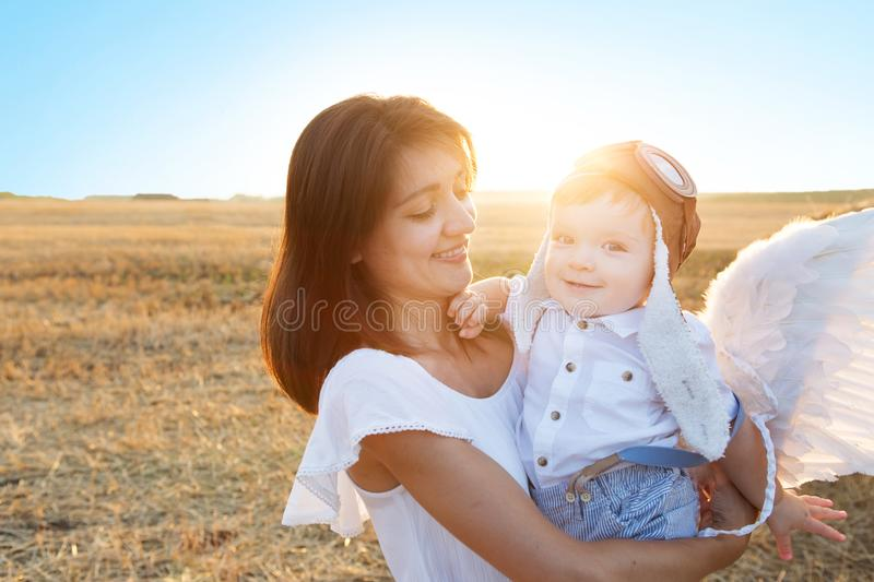 Beautiful mother with son walking in field. Boy in a pilot hat and angel wings sitting on hands of his mother. Beautiful mother with son walking in field. The royalty free stock images