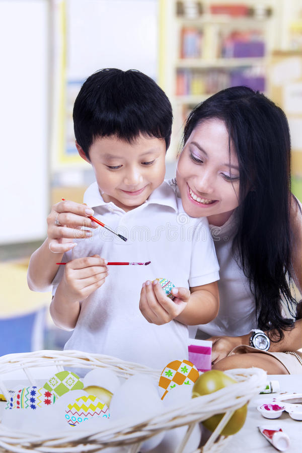 Download Beautiful Mother Teach Son How To Paint Easter Egg Stock Photo - Image: 29363974