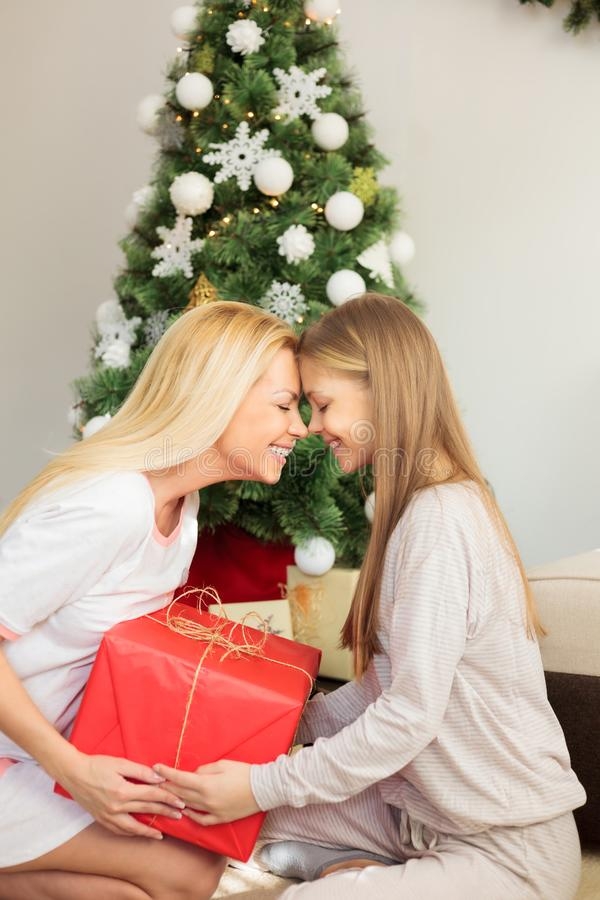 Beautiful mother and teenage daughter tenderly touching foreheads, holding large red Christmas gift royalty free stock photo
