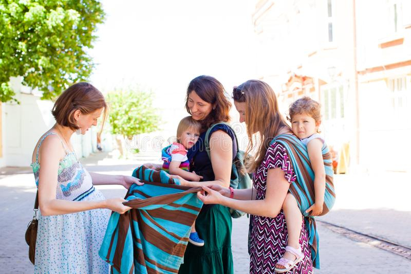 Beautiful mother-to-be looking at sling, baby carrier stock images