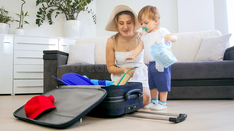 Beautiful young mother with toddler boy packing suitcase for vacation. Beautiful mother with toddler boy packing suitcase for vacation royalty free stock images