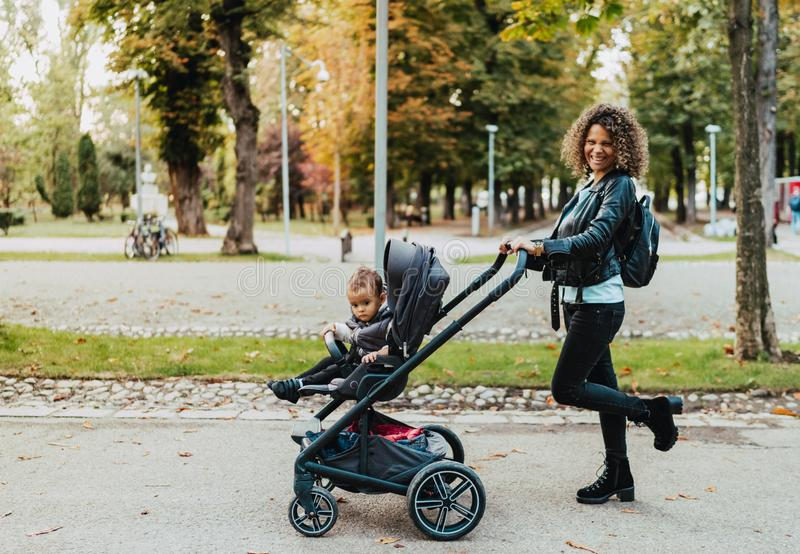 Portrait of beautiful mother walking stroller in park, smiling and walking pram stock images
