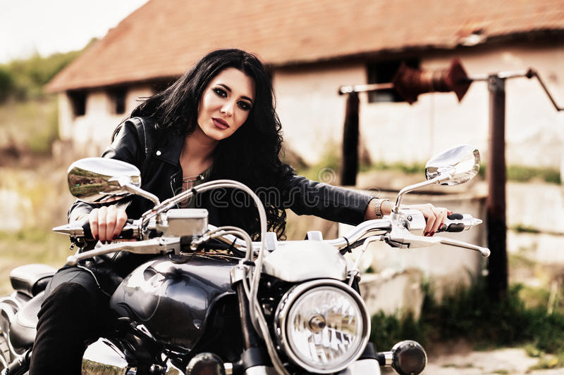 Beautiful motorcycle brunette woman with a classic motorcycle c stock photos