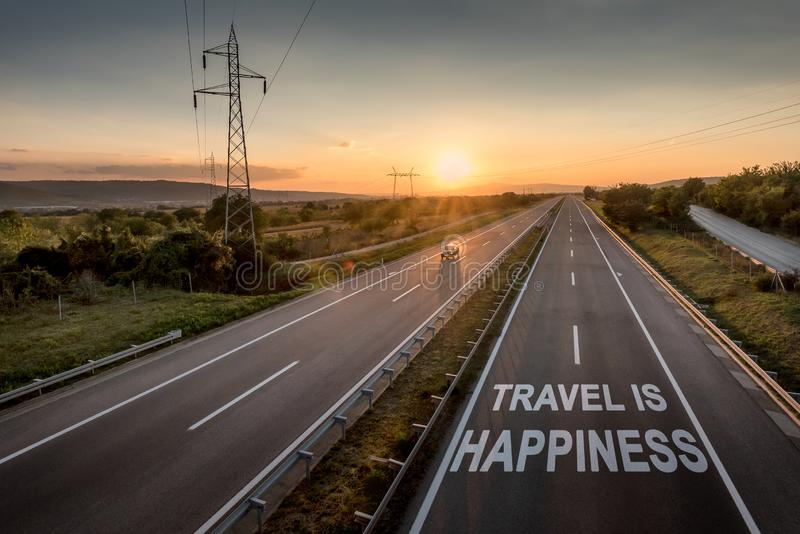 Beautiful Motorway with a Single Car at sunset with motivational message Travel Is Happiness royalty free stock image