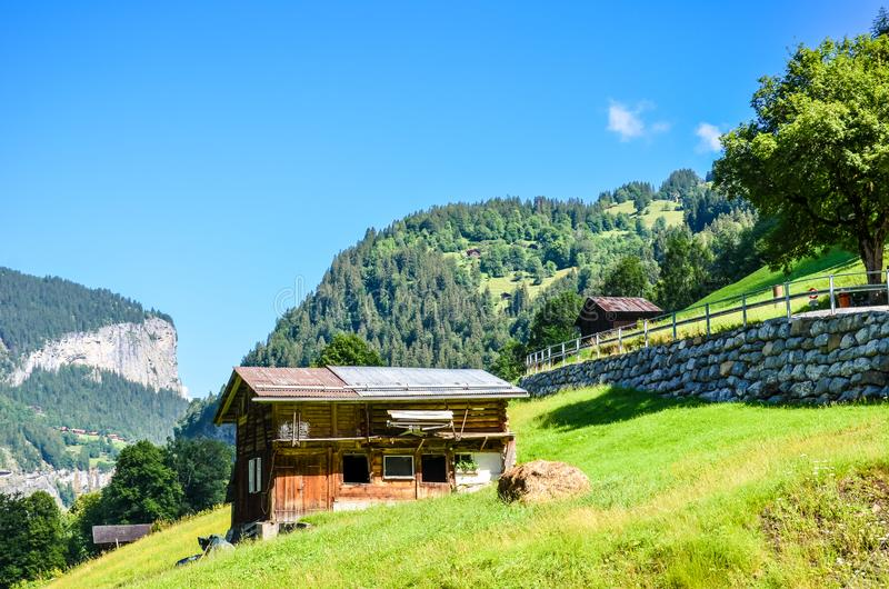 Beautiful mountain hut near Lauterbrunnen in Swiss Alps. Stunning Alpine landscape in summer season. Sunny day, green hills. royalty free stock photography