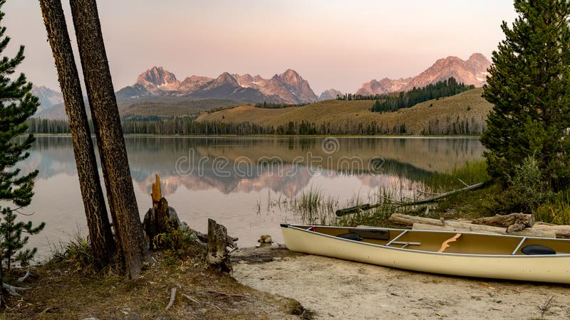 Canoe parked on the shore of an Idaho mountain lake at sunrise stock photography