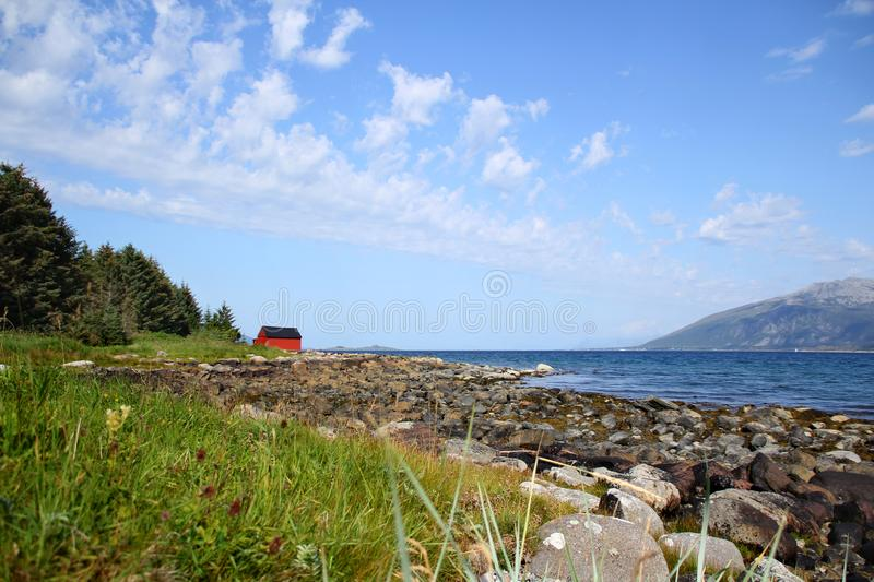 Beautiful mountain landscape with a cute red Scandinavian house on the ocean, Norway royalty free stock photography