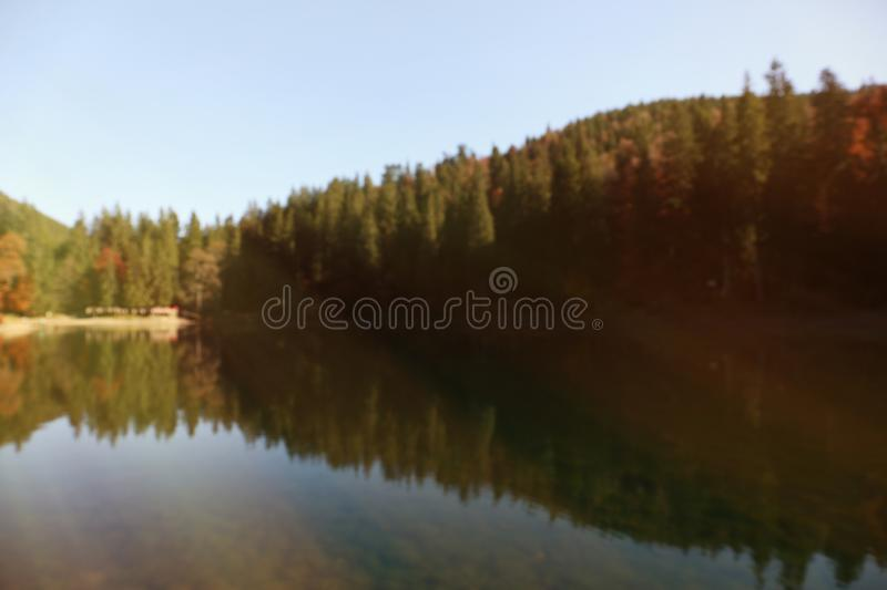 Beautiful mountain landscape with forest near water. Blurred view royalty free stock image