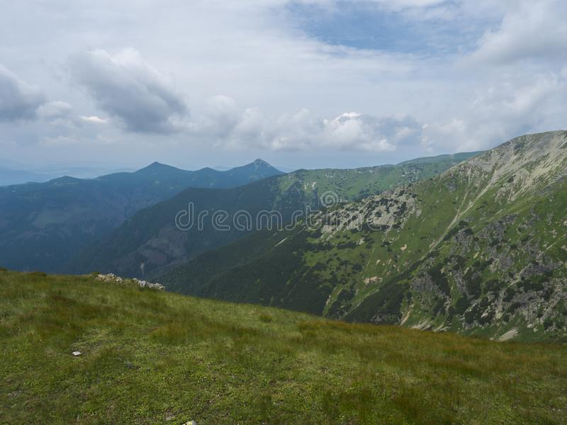 Beautiful mountain landscape with lush green grass, meadow and bare mountain peaks on ridge Western Tatras mountains royalty free stock photo