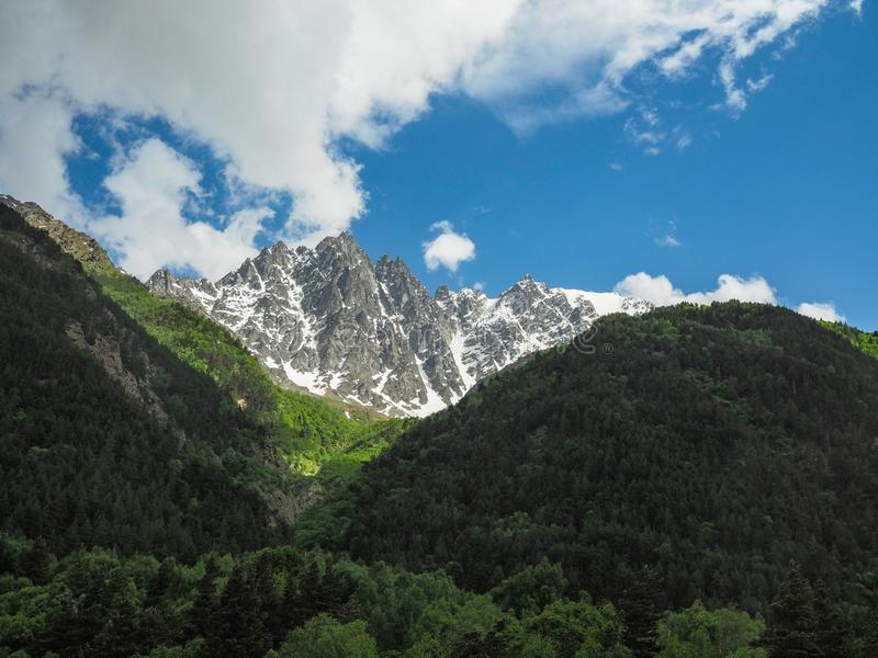 Beautiful mountain landscape with mountains densely covered with forest and coniferous trees and rocky peaks partially royalty free stock photos