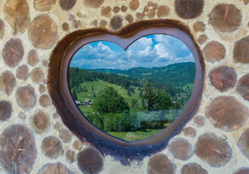 Beautiful mountain landscape reflection trough heart shaped window stock images