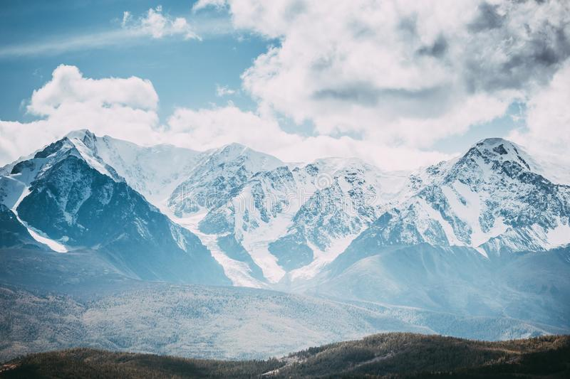 Beautiful mountain range under the clouds. Snowy peaks of rocks stock photography