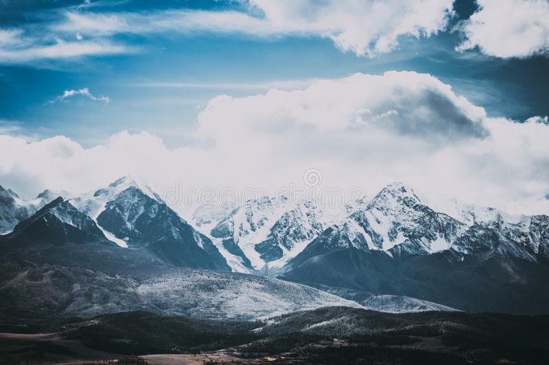 Beautiful mountain range under the clouds. Snowy peaks of rocks. royalty free stock photos