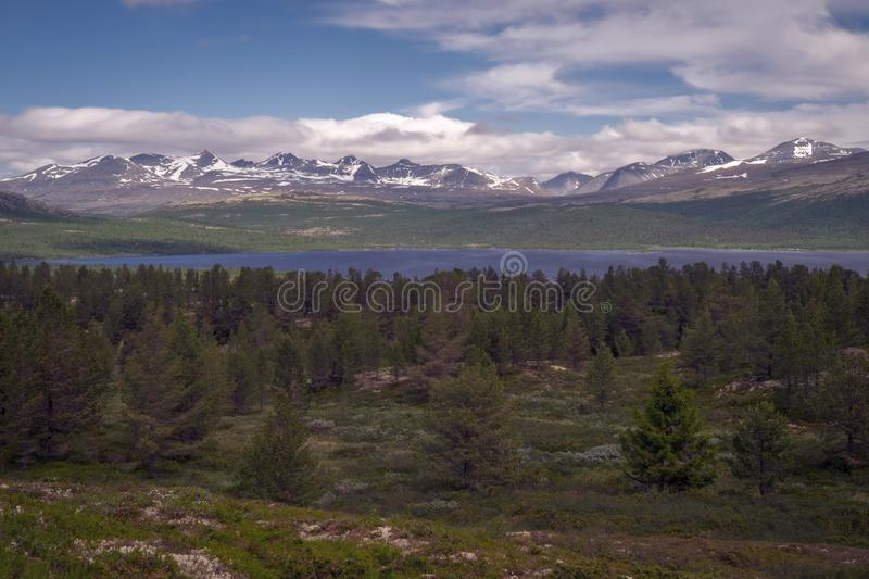 Beautiful mountain scenery over Rondane mountain chain in Norway from Kvam. Forest, nature, snowy peaks, lake, scenic concept stock image