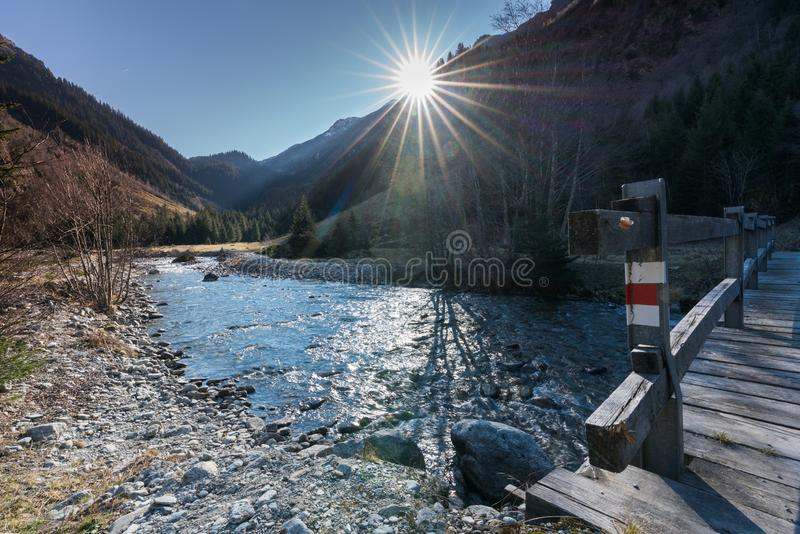 Beautiful mountain stream and peak landscape with the sun shining and a wooden bridge with a hiking trail sign in the foreground. In the Sardasca Valley in the royalty free stock images