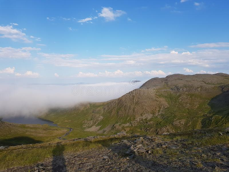 Beautiful mountain view with fog lid over small settlement, mageroya. North cape county royalty free stock photography