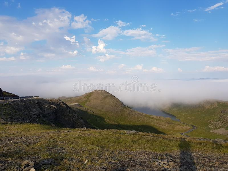 Beautiful mountain view with fog lid over small settlement, mageroya. North cape county stock photo