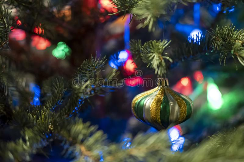 Beautiful multi-colored glass toy on a Christmas tree, on a blurred background of garland. Horizontal photo stock photos